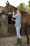 Woman With Horse Outside Stable. Full length side view of a red haired young woman with horse outside stable Royalty Free Stock Photo