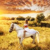 Woman on horse over sunset royalty free stock photos