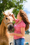 Woman with horse on pony farm Royalty Free Stock Image
