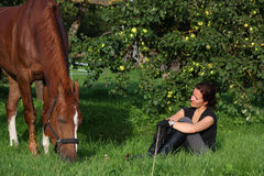 Woman and horse resting at the grazing Stock Photo