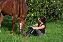Woman and horse resting at the grazing Royalty Free Stock Photography