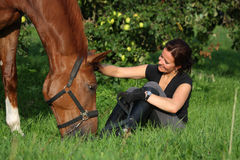 Woman and horse resting at the grazing Stock Image
