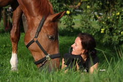 Woman and horse resting at the grazing Royalty Free Stock Images