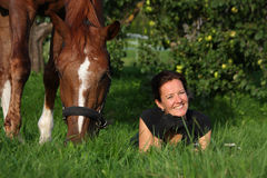 Woman and horse resting at the grazing Stock Photography
