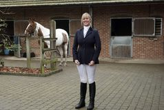 Woman horse rider standing in a stable yard. Smartly dressed horse rider wearing a dark blue riding jacket and white jodhpurs. November 2017 Stock Photo