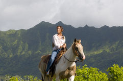 Woman horse riding. Young woman riding a horse in a ranch in Hawaii Stock Photos