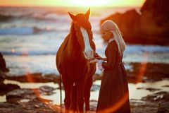 Woman with horse on rocky seashore stock image