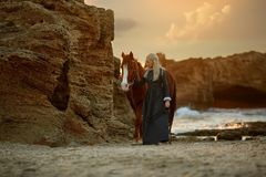 Woman with horse on rocky seashore royalty free stock photos