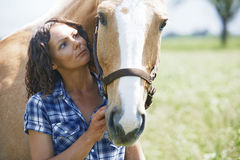 Woman and horse together at paddock stock images