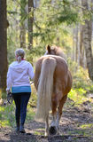 Woman and horse walking Royalty Free Stock Photos