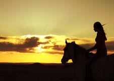 Woman and Horse Watching Sunset Silhouette. Silhouette of a woman riding her horse and watching a beautiful golden sunset with the wind blowing her hair Royalty Free Stock Images
