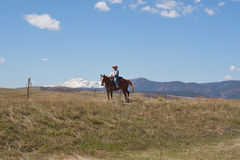 Woman on horseback. Western rider on the way out on the trail in Greenland, Colorado with Pikes Peak in the background Stock Photos