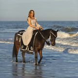 Woman on horseback in ocean. Woman in medieval dress on horseback in ocean royalty free stock photo