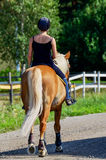 Woman horseback riding. Woman and her horse riding on country road Stock Image