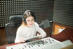 Woman hosting live show on radio. Beautiful young woman with clipboard hosting show live on radio station, sitting in front of sounds mixed console and Royalty Free Stock Image