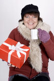 Woman with hot beverage and christmas present Stock Image