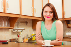 Woman with hot coffee beverage. Caffeine. Woman sitting in kitchen with cup of coffee. Young girl and hot energizing beverage that keeps her awake. Energy and Stock Photography