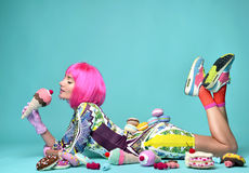 Woman in hot pink party wig eating fake ice cream and sweet cand. Beautiful funky fashion cheerful woman in hot pink party wig eating fake ice cream and sweet Royalty Free Stock Image