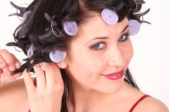 Woman and Hot Rollers. Young woman styling her hair with hot rollers royalty free stock photos