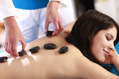 Woman hot stone treatment Stock Images