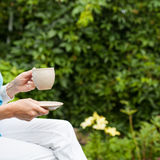Woman with hot tea. Beautiful woman with hot tea in the garden Stock Photos
