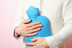 Woman with hot water bottle Royalty Free Stock Image