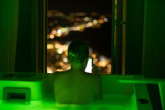 Woman in hotel bathroom reading on tablet royalty free stock photos