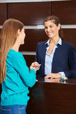 Woman at hotel reception giving key card Stock Image