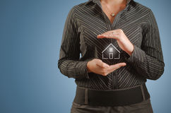 Businesswoman banker holding home in hands Royalty Free Stock Image