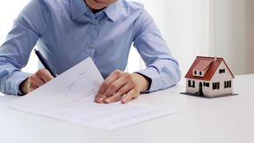 Woman with house model and pen signing contract stock footage