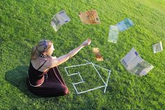 Woman with a house and money Stock Photography