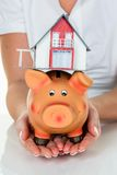 Woman with house and piggy bank Stock Photo