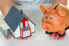 Woman with house and piggy bank. A woman with a house and a piggy bank. the right financing for the home purchase Royalty Free Stock Photography