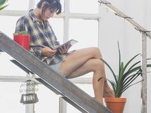 Woman on house stairs relaxing, reading email on a tablet. Woman on house stairs relaxing, reading email on mobile wifi connection Royalty Free Stock Photos