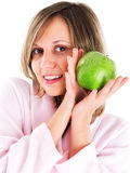 Woman in housecoat with apple Stock Photography
