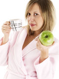 Woman in housecoat with coffee and apple Royalty Free Stock Photo
