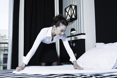 Woman housekeeper doing bed in a hotel bedroom. Beautiful caucasian woman housekeeper doing bed in a hotel bedroom Stock Photography