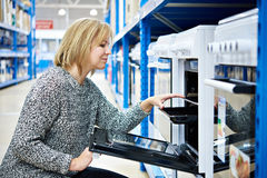 Woman housewife chooses gas stove in the shop appliances Royalty Free Stock Photo