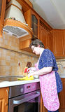 Woman housewife cleans the cooktop surface Royalty Free Stock Photos