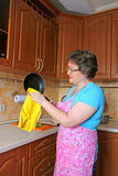 Woman housewife cleans the pan Royalty Free Stock Photos