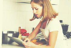 Woman housewife cooks food a recipe from Internet with a tablet Royalty Free Stock Photos