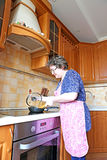 Woman housewife fry food in a pan Royalty Free Stock Images
