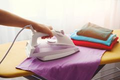 The woman the housewife irons clothes at home. On the Ironing Board iron and purple t-shirt, as well as other things of different stock photos