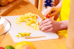Woman housewife in kitchen cutting apple fruits Stock Image