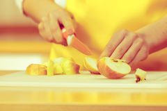 Woman housewife in kitchen cutting apple fruits Stock Photo