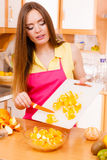 Woman housewife in kitchen cutting orange fruits Stock Image