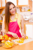 Woman housewife in kitchen cutting orange fruits Royalty Free Stock Photos