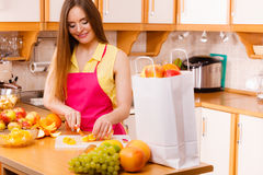 Woman housewife in kitchen cutting orange fruits Royalty Free Stock Photography