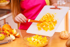 Woman housewife in kitchen cutting orange fruits Stock Photography