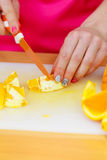 Woman housewife in kitchen cutting orange fruits Stock Images